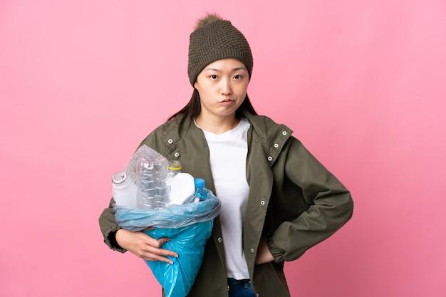 Китайская девушка держит сумку, полную пластиковых бутылок для переработки, изолированные