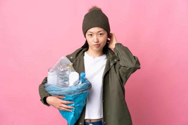 고립 된 재활용 플라스틱 병의 전체 가방을 들고 중국 소녀