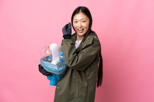 勝利を祝う孤立したピンクでリサイクルするペットボトルの完全な袋を保持している中国の女の子