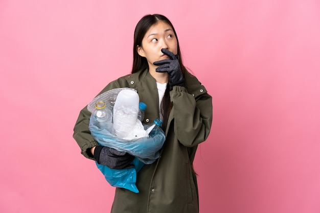 Китайская девушка держит мешок, полный пластиковых бутылок, чтобы утилизировать на изолированных розовый с сомнением лица и выражение лица