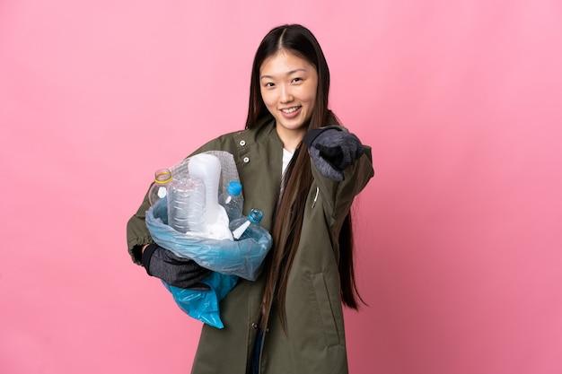 幸せな表情で孤立したピンクのポインティングフロントでリサイクルするペットボトルの完全な袋を保持している中国の女の子
