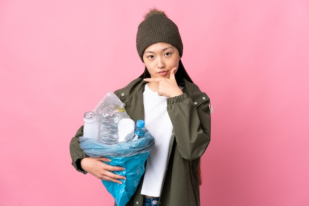 孤立したピンクの思考でリサイクルするためにペットボトルでいっぱいのバッグを保持している中国の女の子