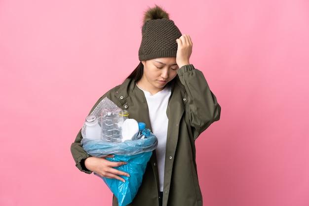 頭痛のある孤立したピンクでリサイクルするためにペットボトルでいっぱいのバッグを保持している中国の女の子