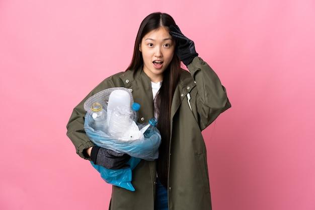 Китайская девушка держит сумку, полную пластиковых бутылок для переработки, на изолированном розовом с удивленным выражением лица