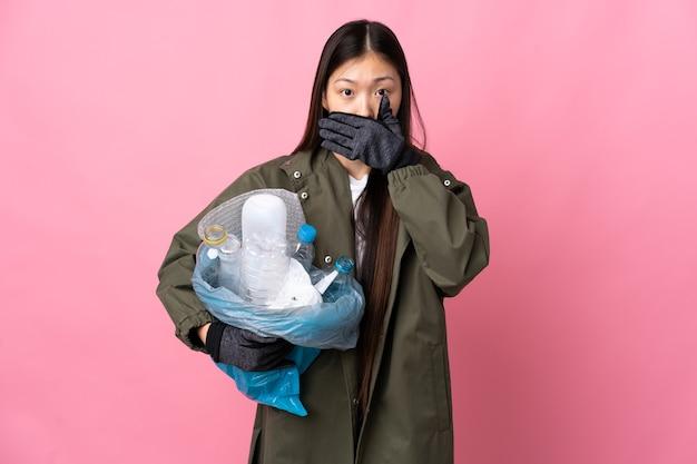 手で孤立したピンクのカバー口の上にリサイクルするためにペットボトルでいっぱいのバッグを保持している中国の女の子