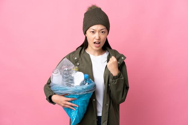 Китайская девушка с сумкой, полной пластиковых бутылок для переработки изолированного розового цвета, разочарована плохой ситуацией
