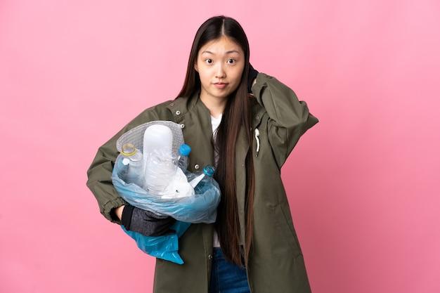 欲求不満で耳を覆っている孤立したピンクの壁の上でリサイクルするためにペットボトルでいっぱいのバッグを持っている中国の女の子