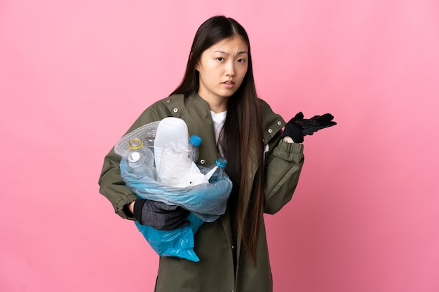 플라스틱 병으로 가득 찬 가방을 들고 중국 소녀는 의심을 갖는 고립 된 분홍색 벽 위에 재활용
