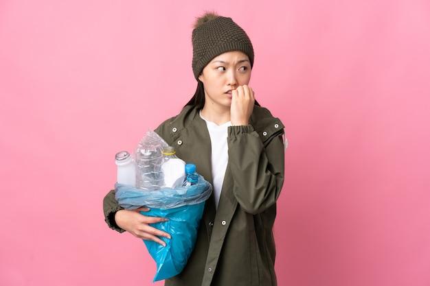 고립 된 분홍색 벽을 통해 재활용 플라스틱 병으로 가득 찬 가방을 들고 중국 소녀 긴장하고 입에 손을 넣어 무서워