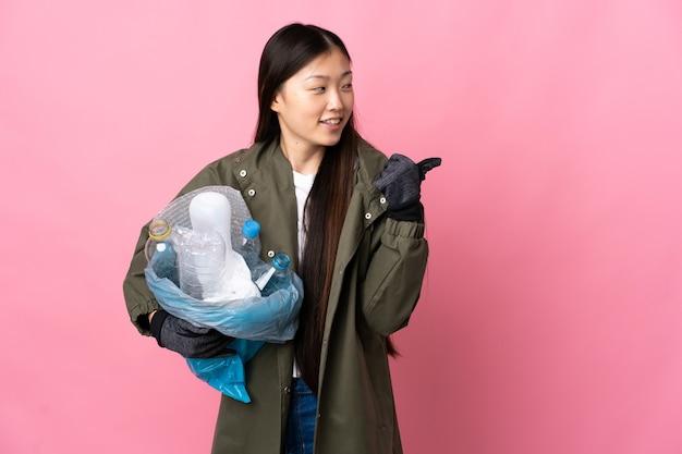 제품을 제시하기 위해 측면을 가리키는 격리 된 분홍색 벽 위에 재활용 플라스틱 병으로 가득 찬 가방을 들고 중국 소녀