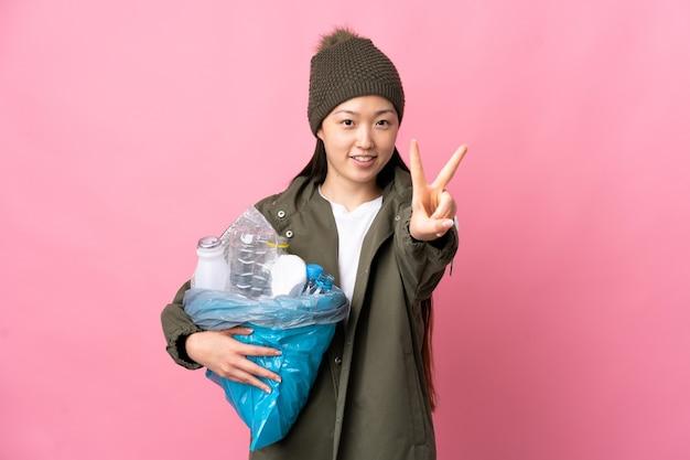 플라스틱 병으로 가득 찬 가방을 들고 중국 소녀가 웃고 승리의 기호를 보여주는 고립 된 분홍색 벽 위에 재활용