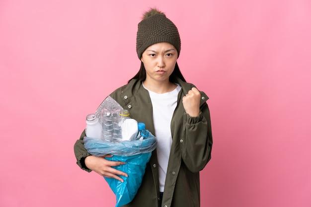 不幸な表情で孤立したピンクの壁をリサイクルするためにペットボトルでいっぱいのバッグを保持している中国の女の子
