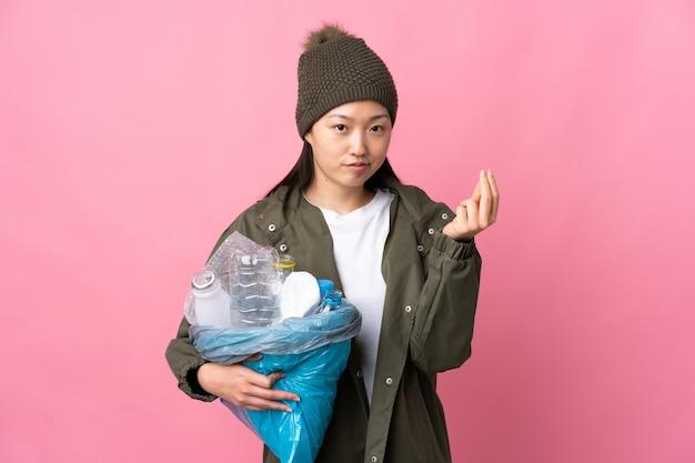 이탈리아 제스처를 만드는 분홍색 위에 재활용 플라스틱 병으로 가득 찬 가방을 들고 중국 소녀