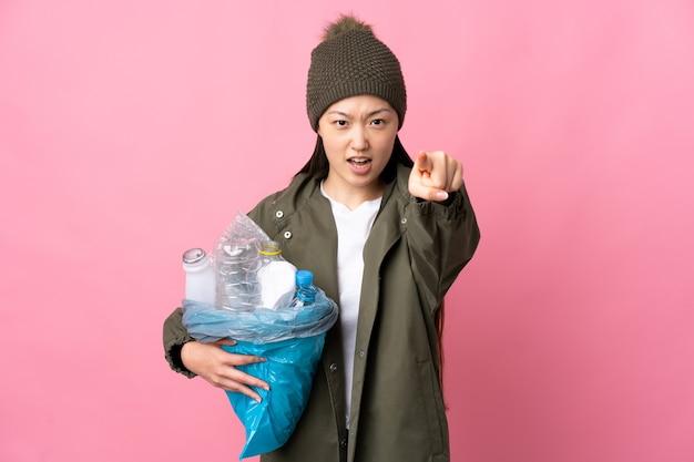 Китайская девушка держит мешок, полный пластиковых бутылок для переработки
