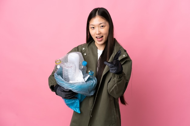 Chinese girl holding a bag full of plastic bottles to recycle over pink pointing to the front and smiling