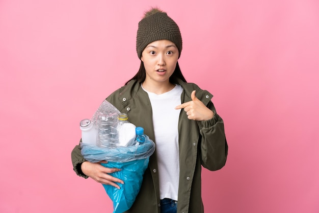 Chinese girl holding a bag full of plastic bottles to recycle over pink pointing to oneself