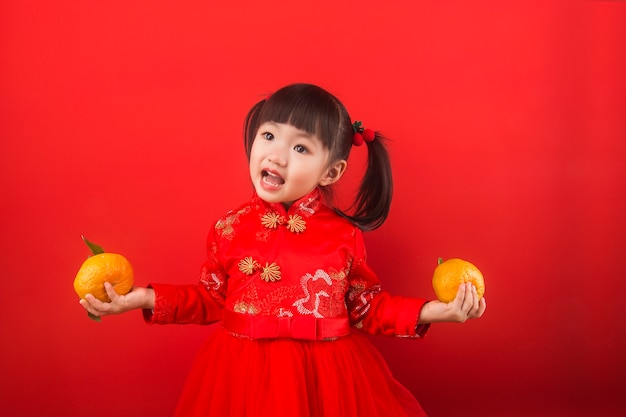 A chinese girl holding oranges for the spring festival