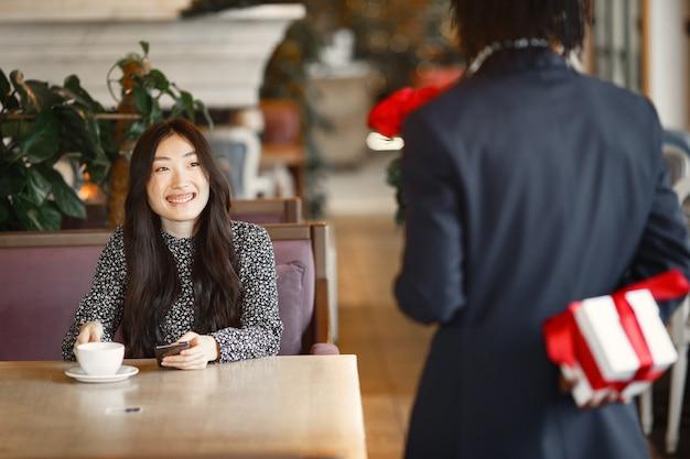 電話で中国の女の子。黒人は驚きを準備しています。テーブルで幸せな女の子