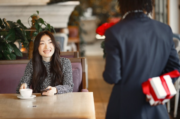 Ragazza cinese con il telefono. il ragazzo nero sta preparando una sorpresa. ragazza felice al tavolo