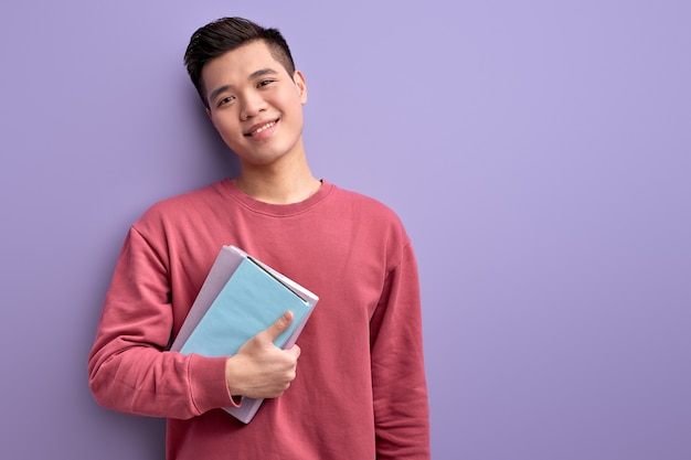 Chinese guy with book in hands enjoy education and university, posing