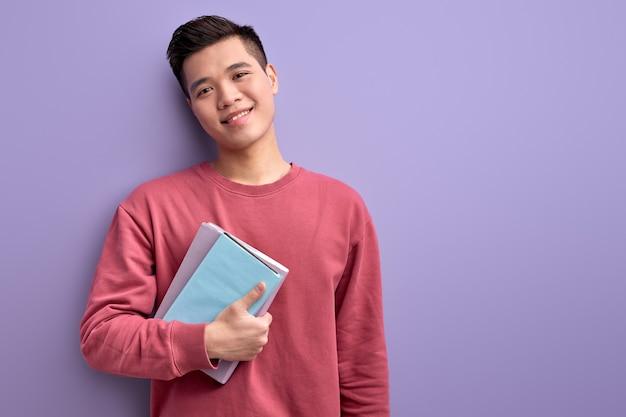 Китайский парень с книгой в руках наслаждается образованием и университетом, позирует