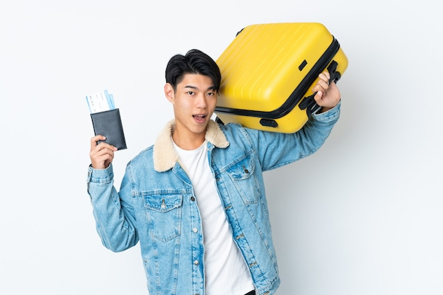 Chinese over isolated wall in vacation with suitcase and passport