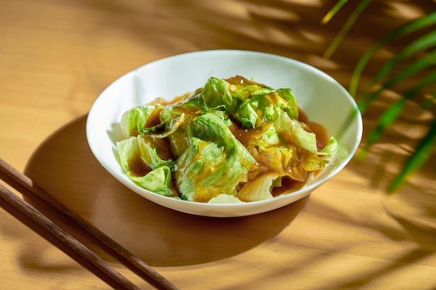 オイスターソースのチャイニーズレタスサラダと白いプレートにニンニク