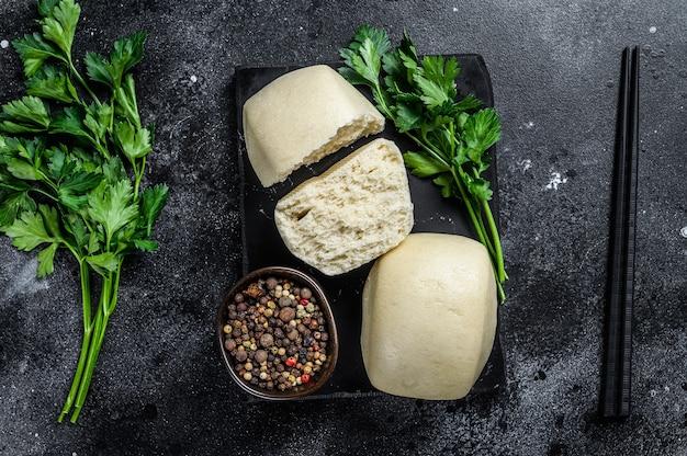 中華の蓮ペースト蒸しパン。黒の背景。上面図。