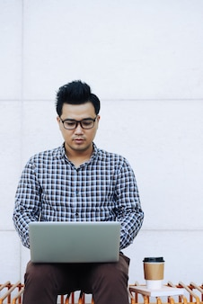 Chinese man in glasses sitting on bench outdoors and using laptop