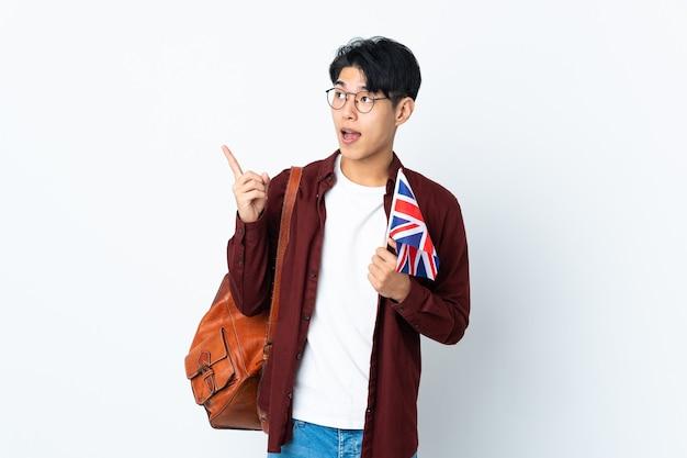 指を持ち上げながら解決策を実現しようと紫の壁に分離された英国の旗を保持している中国人男性