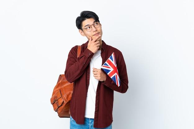 笑顔で見上げる紫色の壁に分離された英国の旗を保持している中国人男性