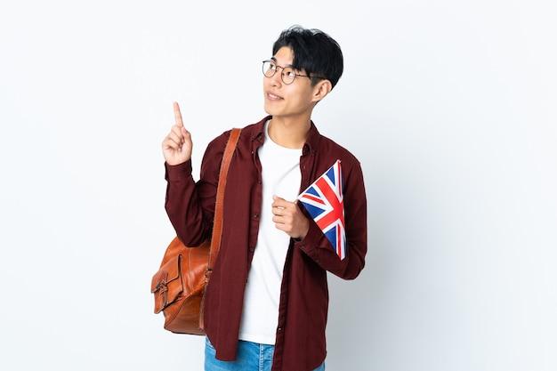 素晴らしいアイデアを指している紫色の壁に分離された英国の旗を保持している中国人男性