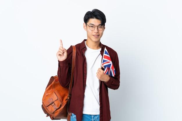 紫色の壁に分離された英国の旗を持っている中国人男性が最高の兆候を示して指を持ち上げる
