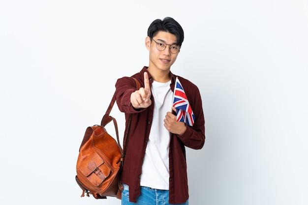 紫色の表示と指を持ち上げて英国の旗を保持している中国人男性