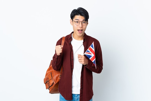 Chinese man holding an uk flag isolated on purple background celebrating a victory in winner position