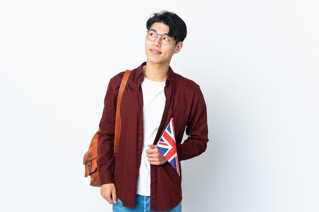 Chinese man holding an uk flag isolated on purple wall thinking an idea while looking up