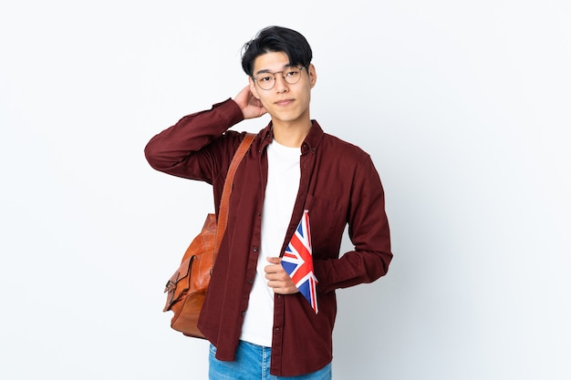 Chinese man holding an uk flag on purple having doubts
