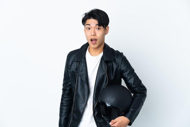 Китаец в мотоциклетном шлеме изолирован на белой стене с удивленным выражением лица