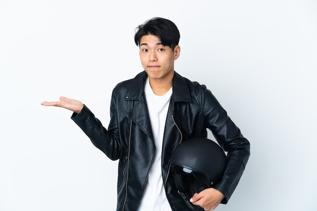 Chinese man with a motorcycle helmet on white having doubts while raising hands