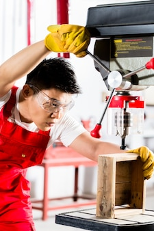Chinese man working with drill in factory