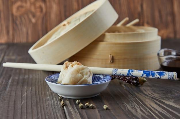 竹蒸し器に箸と点心を入れた中華肉団子蒸し料理。