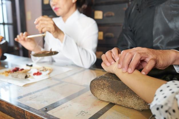 Практикующий китайской медицины измеряет пульс клиента