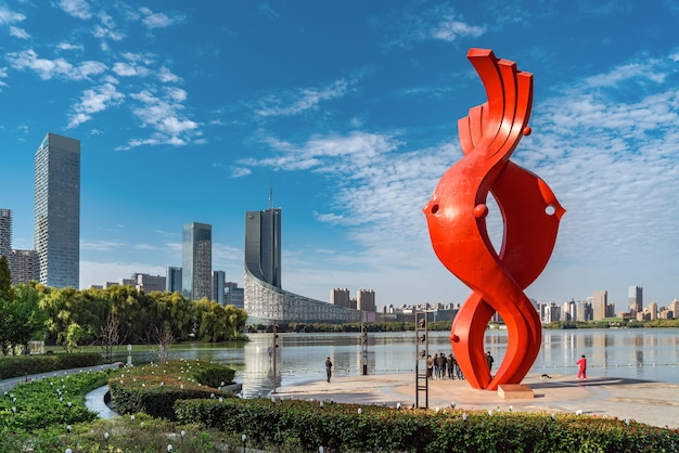 Chinese modern city with red abstract sculpture by the river
