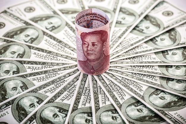 Китайские деньги, женьминьби, банкнота в 100 юаней, зажатая в уголках многих стодолларовых купюр