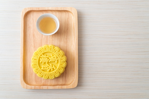 Chinese moon cake custard flavour with tea on wood plate