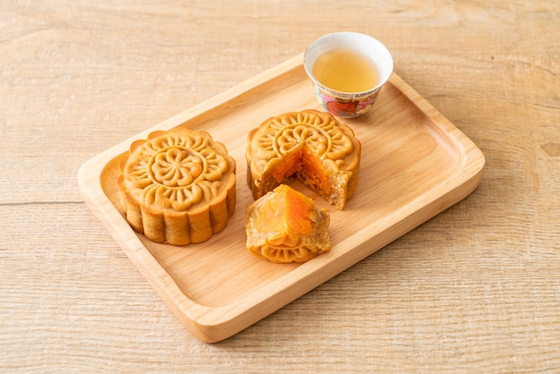 Китайский лунный пирог со вкусом дуриана и яичного желтка с чаем на деревянной тарелке