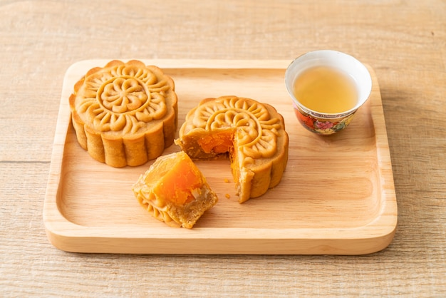 Chinese moon cake durian and egg yolk flavour with tea on wood plate