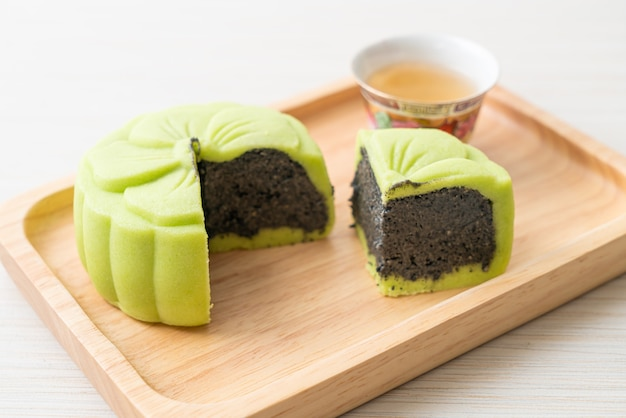木製のトレイにお茶と中国の月餅緑茶味