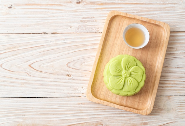 Chinese moon cake green tea flavour with tea on wood plate