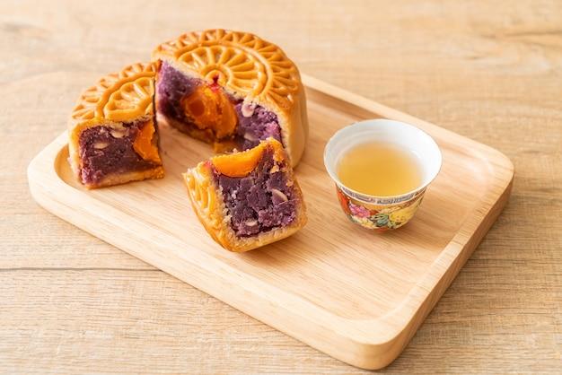 木の板にお茶と中国の月餅紫芋味